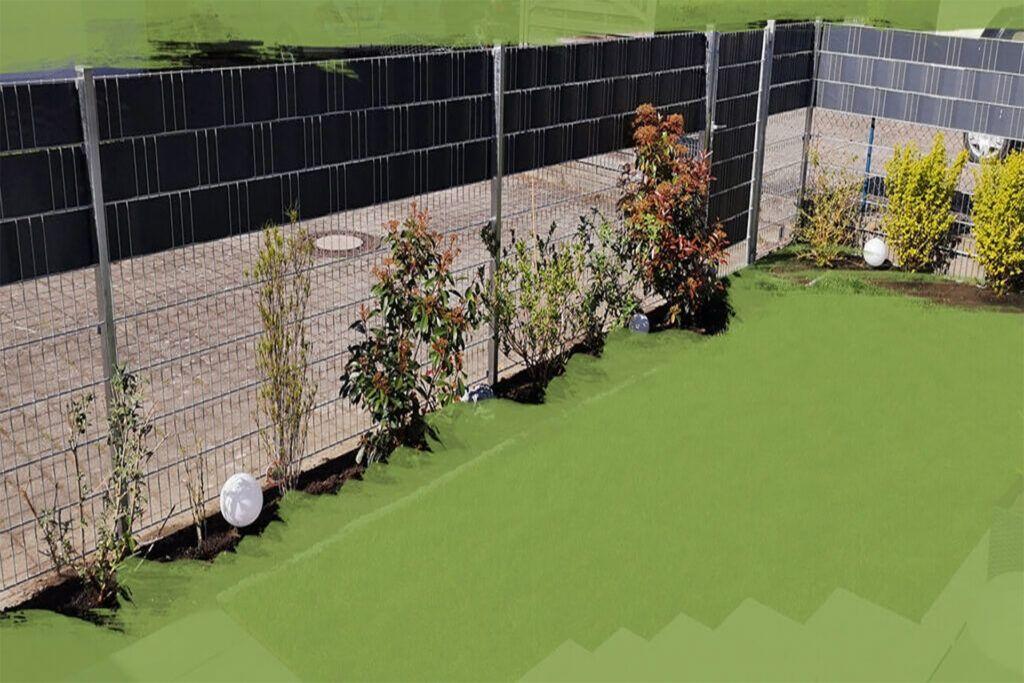 Zaunpfosten montieren - Ein Gartenzaun, der ein Rasenstück über Eck umschließt